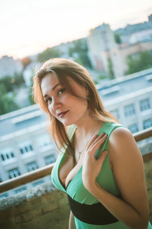 Jeune belle fille d'une forte poitrine dans la robe verte avec images libres de droits