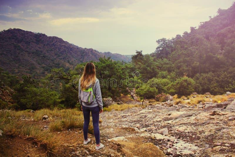 Jeune belle fille dans la chemise de hoodie et le sac à dos touristique regardant sur le paysage étonnant de la montagne de Hemer images stock