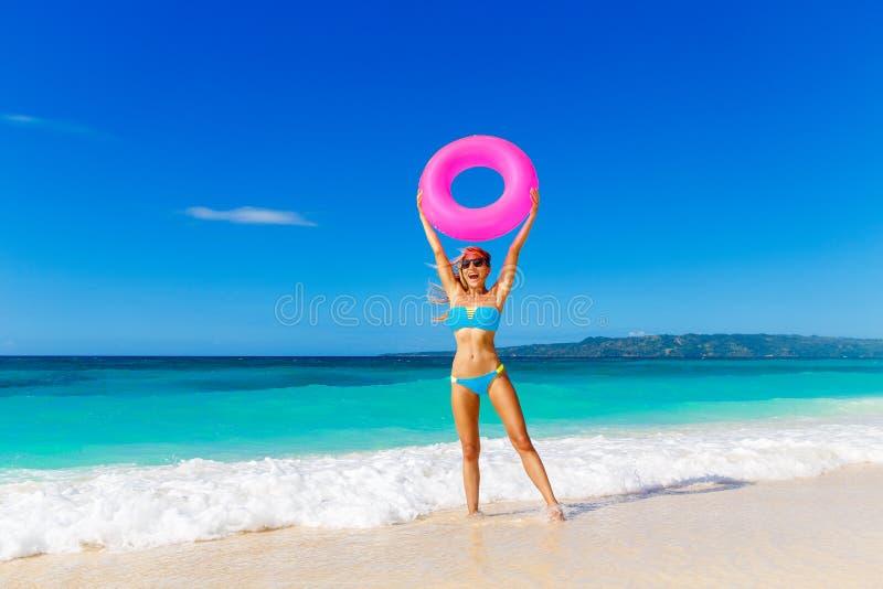 Jeune belle fille dans le bikini bleu ayant l'amusement sur un bea tropical photos libres de droits