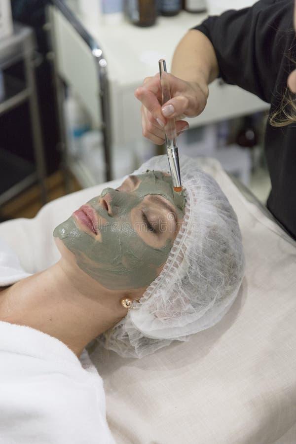 Jeune belle fille dans le masque vert pour le visage détendant dans le salon de station thermale images libres de droits