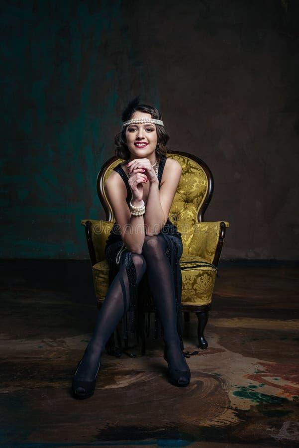 Jeune belle fille dans le style rouge de robe 20 du ` s ou 30 ` s avec le verre de martini près du piano Femme de style de vintag images stock