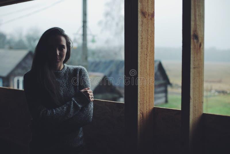 Jeune belle fille dans le village Modèle sur le fond d'une maison en bois dans le village Lumière foncée photo stock