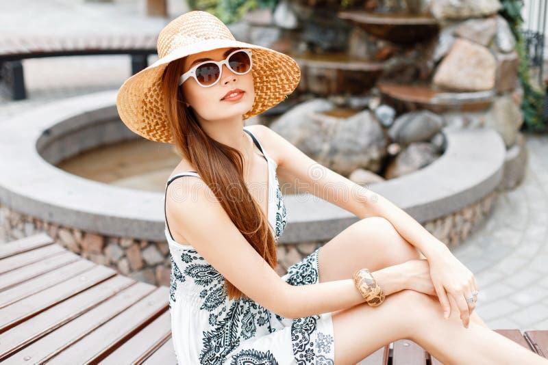 Jeune belle fille dans les lunettes de soleil et le chapeau de paille presque se reposant photographie stock libre de droits