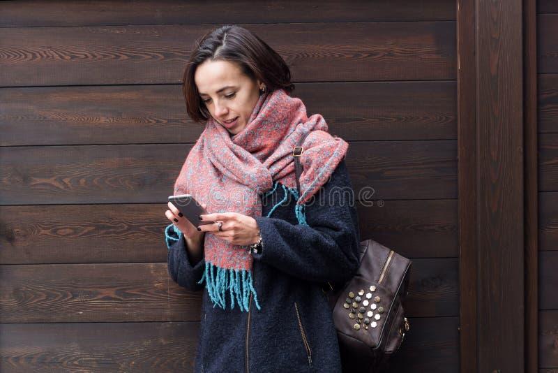Jeune belle fille dans un manteau et une écharpe utilisant le téléphone portable photographie stock