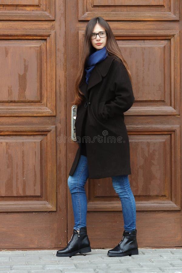 Jeune belle fille dans un manteau noir et une écharpe bleue ayant l'amusement Fille élégante de brune avec les cheveux extra-long photo stock