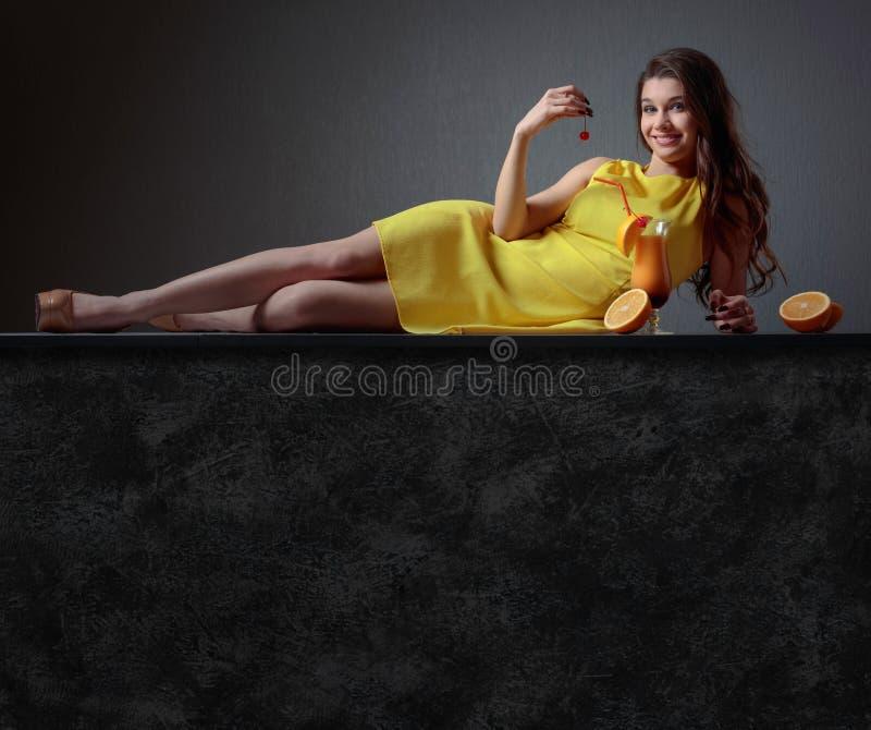 Jeune belle fille dans une robe jaune avec la tequila Sun de cocktail images stock