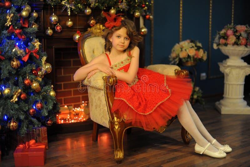Jeune belle fille dans une robe rouge à côté de la cheminée dans Noël image libre de droits