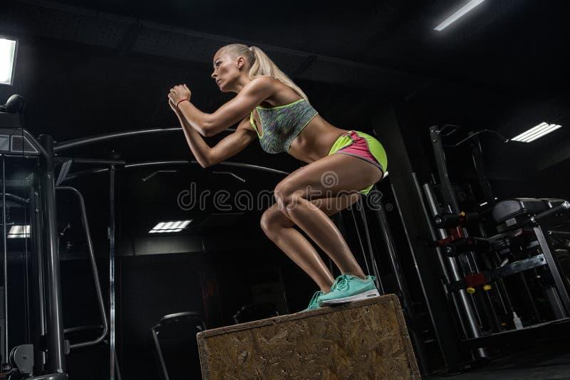 Jeune belle fille de bodybuilding faisant des exercices en GY moderne image libre de droits