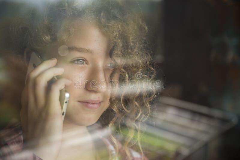 Jeune belle fille de femme s'asseyant à la maison et entretien avec le portable Image modifiée la tonalité, bruit supplémentaire image libre de droits