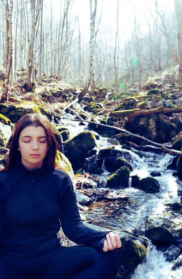 Jeune belle fille de foyer faisant le lotus de pose de yoga se reposant dans une roche sur une rivière méditant dans la forêt ave image libre de droits