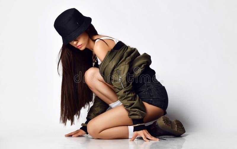 Jeune belle fille de hippie s'asseyant sur son plein corps de genoux en bref les bottes élégantes modernes et le chapeau de veste image stock