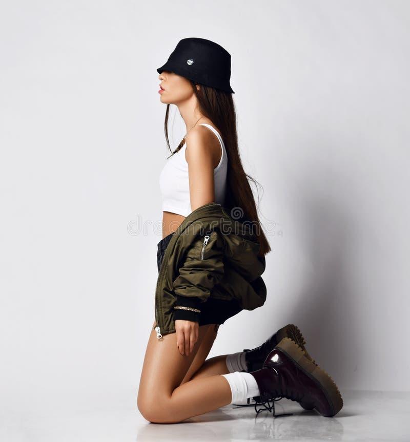 Jeune belle fille de hippie s'asseyant sur son plein corps de genoux en bref les bottes élégantes modernes et le chapeau de veste photos stock