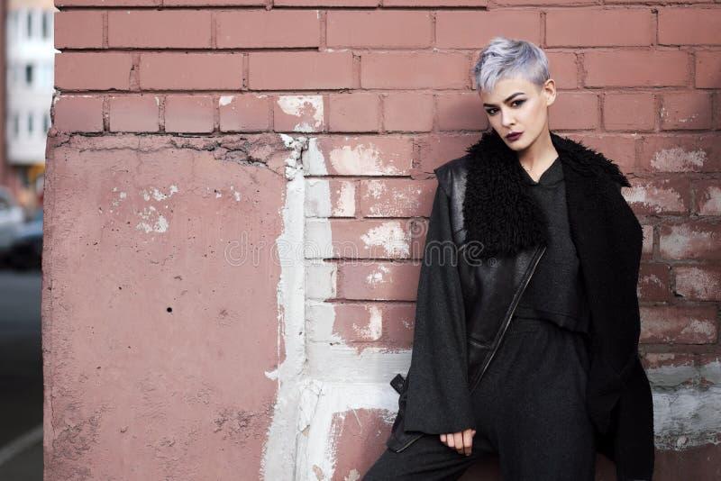Jeune belle fille de mode tirant dehors près du mur de briques à la maison photographie stock