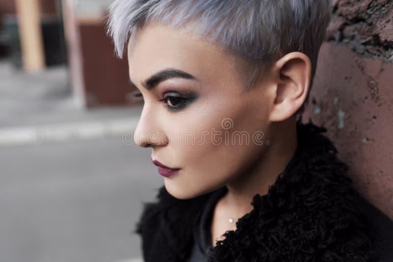 Jeune belle fille de mode tirant dehors près du mur de briques à la maison image libre de droits
