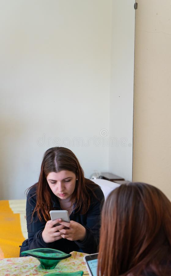Jeune belle fille européenne s'asseyant sur le lit pensivement utilisant seul le temps de dépense de téléphone portable dans la c images stock