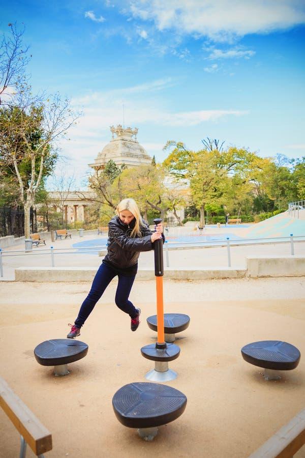 Jeune belle fille faisant des exercices sur l'au sol de sports de rue image libre de droits
