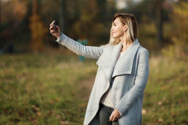 Jeune belle fille faisant le selfie en parc Fond d'automne photos libres de droits