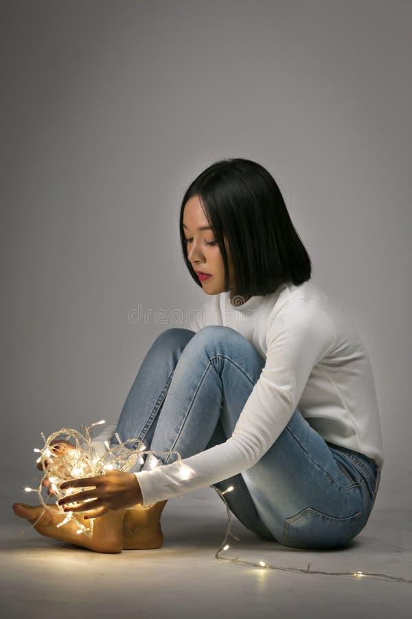 Jeune belle fille jouant avec la lumière menée image stock