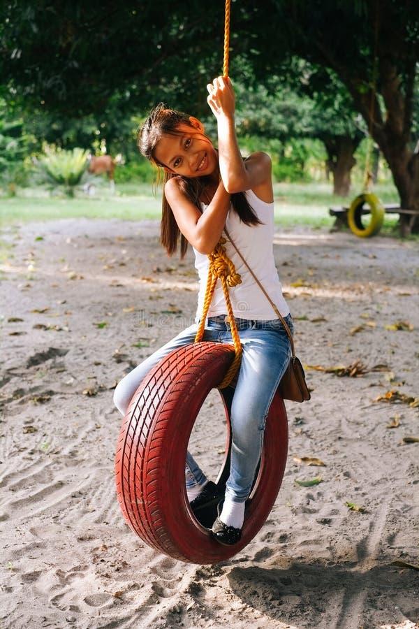 Jeune belle fille jouant sur l'oscillation de pneu dans la ferme images libres de droits