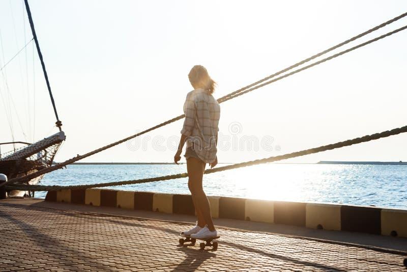 Jeune belle fille marchant au bord de la mer, faisant de la planche à roulettes photographie stock