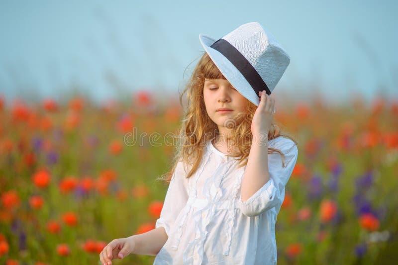 Jeune belle fille posant dans un chapeau près du fie de floraison de pavot photographie stock libre de droits