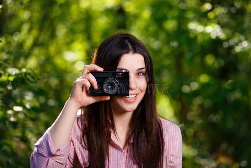 Jeune belle fille prenant des photos avec le rétro appareil-photo de film dans photographie stock