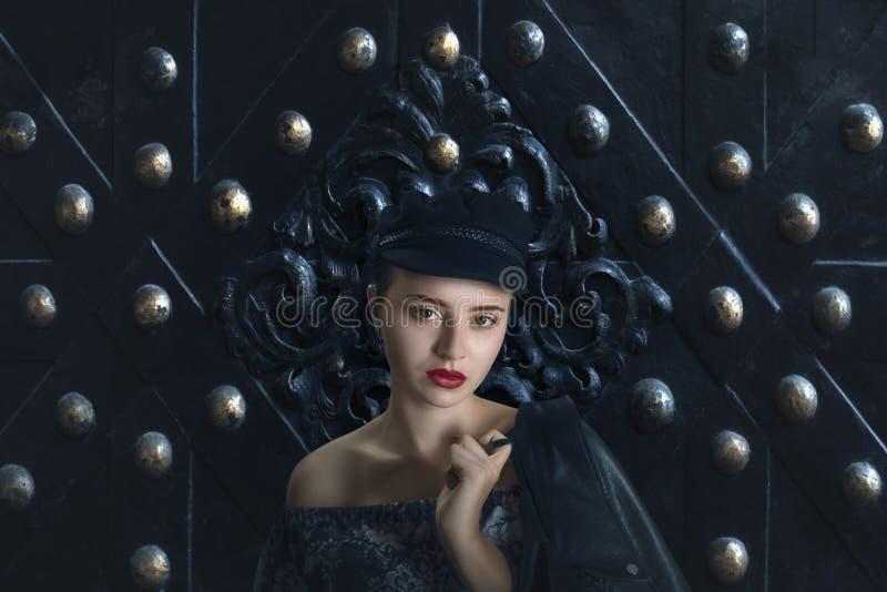 Jeune belle fille rousse dans le chapeau noir avec la veste en cuir photos stock