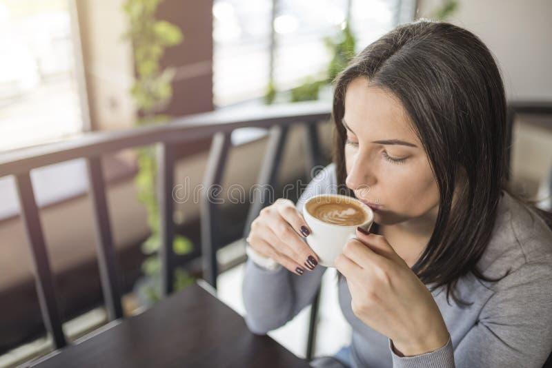 Jeune belle fille s'asseyant dans le café et appréciant le café photos stock
