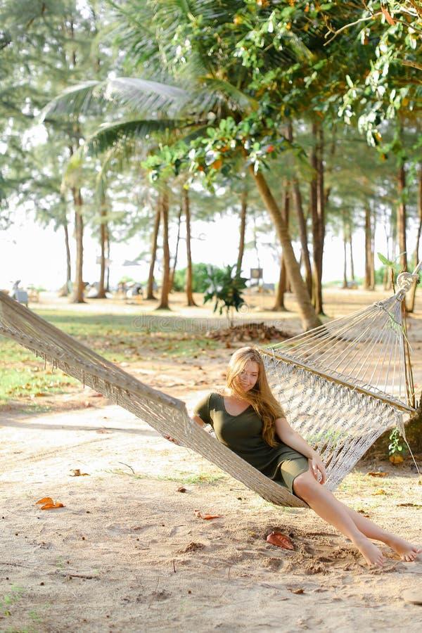Jeune belle fille s'asseyant nu-pieds sur l'hamac, le sable et les arbres en osier à l'arrière-plan photos stock