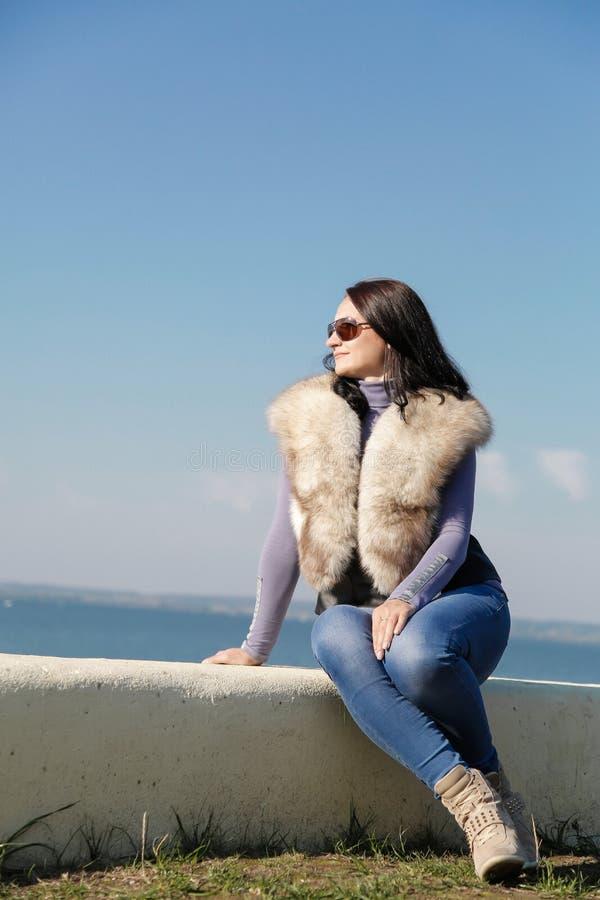 Jeune belle fille s'asseyant sur le rivage de la mer bleue images stock