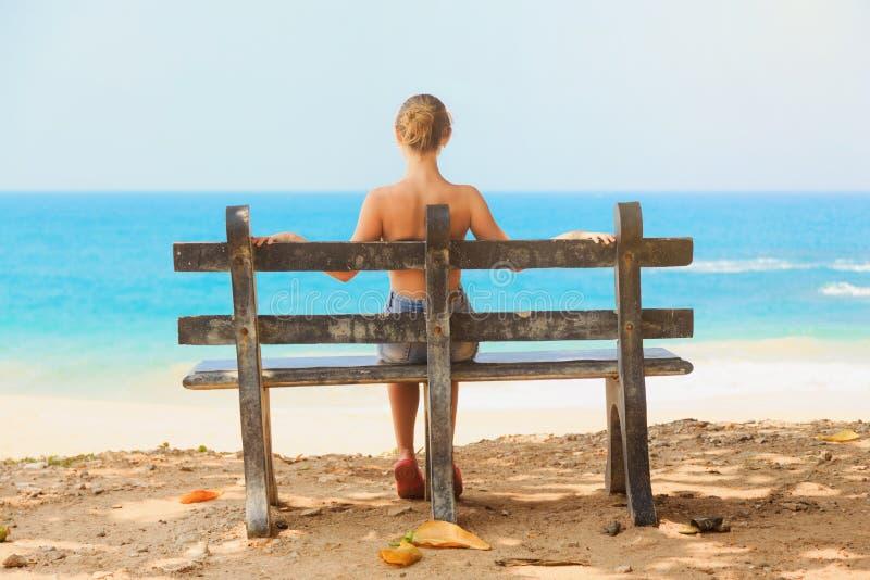 Jeune belle fille s'asseyant sur un banc sur la plage photographie stock