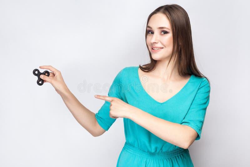 Jeune belle fille se tenant et jouant avec le fileur de personne remuante images libres de droits