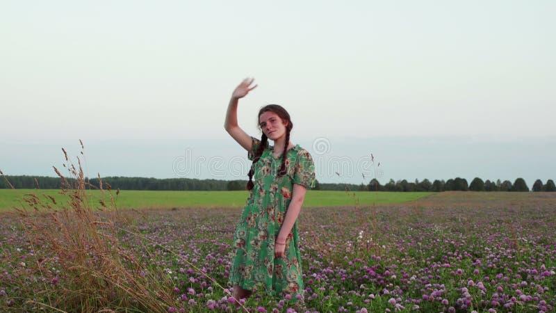 Jeune belle fille se tenant sur un pré des trèfles et des vagues au coucher du soleil banque de vidéos