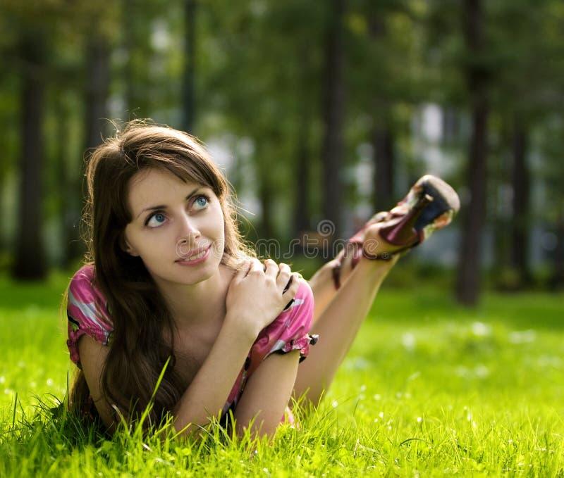 Jeune belle fille sur une herbe photographie stock libre de droits