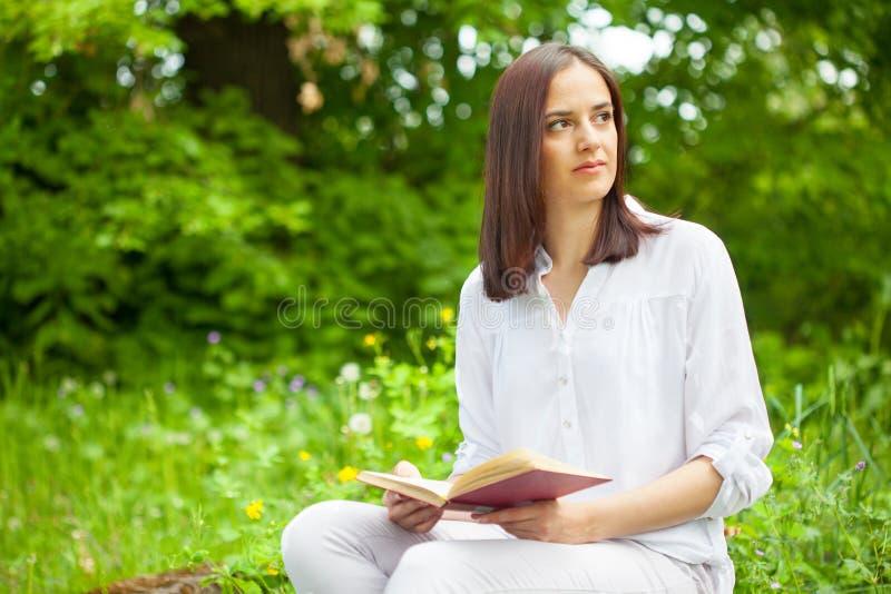 Jeune, belle fille tenant un livre ouvert en parc vert d'été photographie stock libre de droits