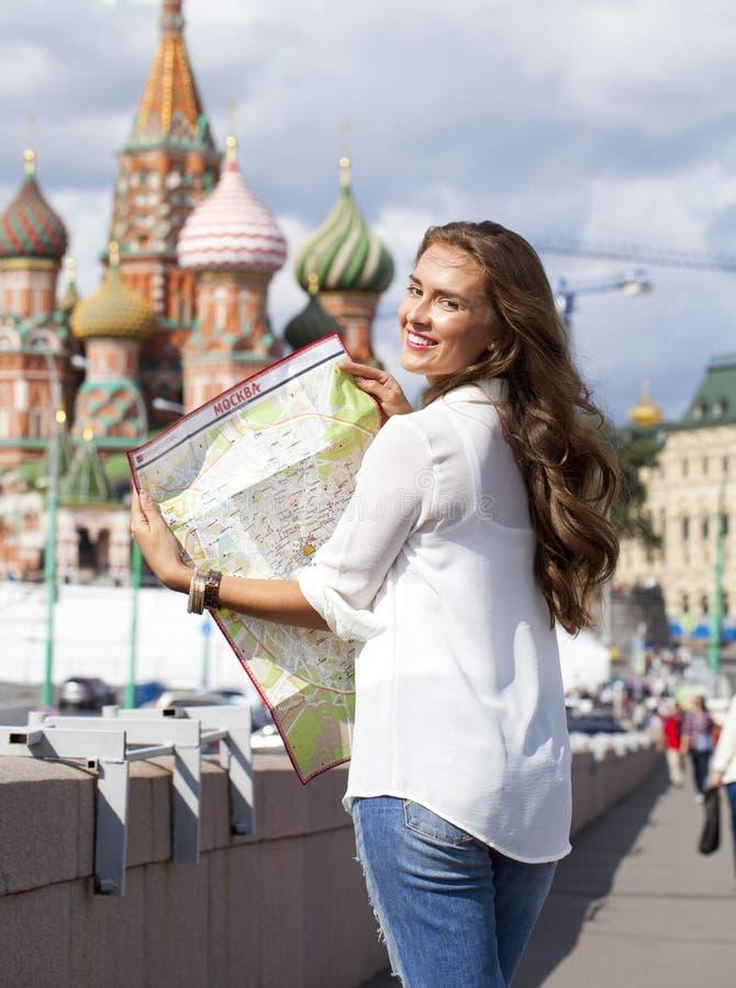Jeune belle fille tenant une carte de touristes de Moscou photo libre de droits