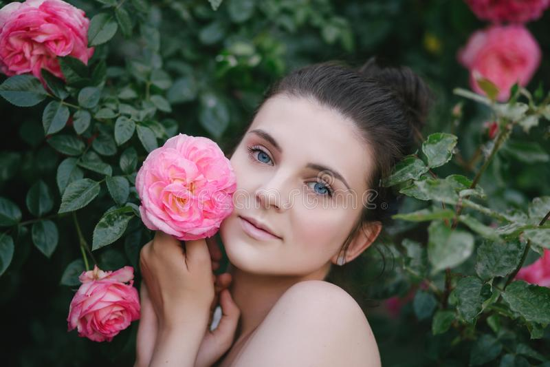 Jeune belle fin de portrait de femme vers le haut de la pose avec les fleurs roses de roses dans un jardin photo stock