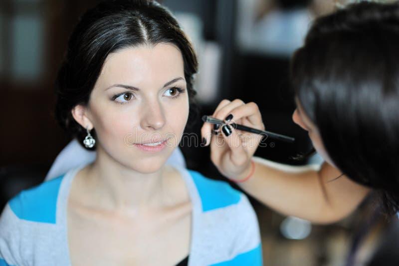 Jeune belle jeune mariée appliquant le maquillage de mariage par l'artiste de maquillage images libres de droits
