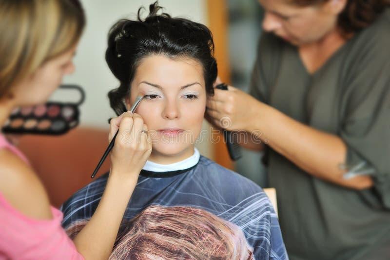 Jeune belle jeune mariée appliquant le maquillage de mariage par l'artiste de maquillage photo stock