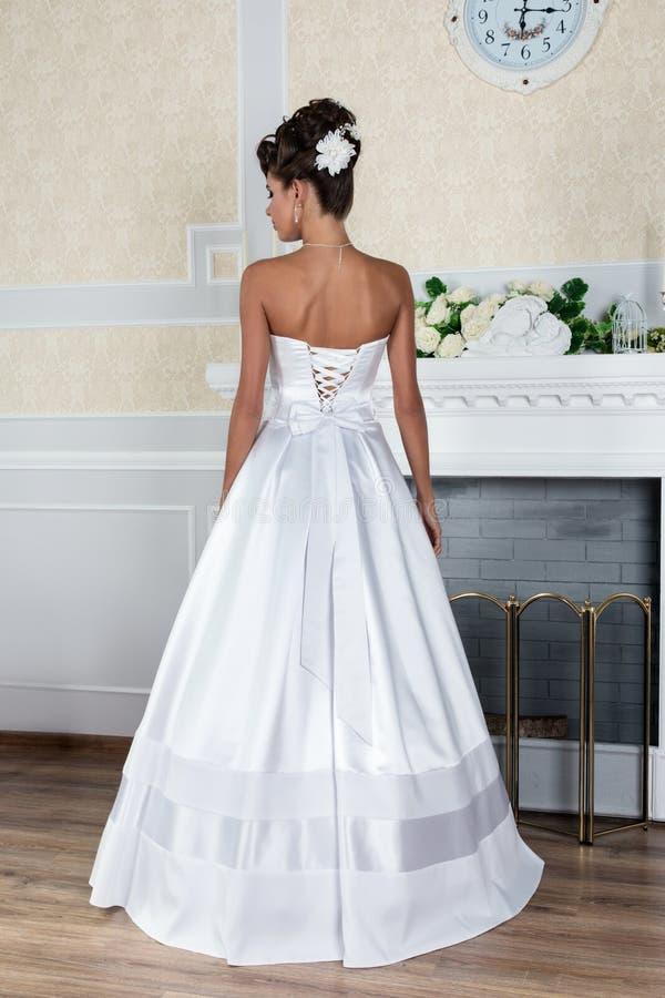 Jeune belle jeune mariée se tenant dans la robe de mariage luxueuse photo libre de droits