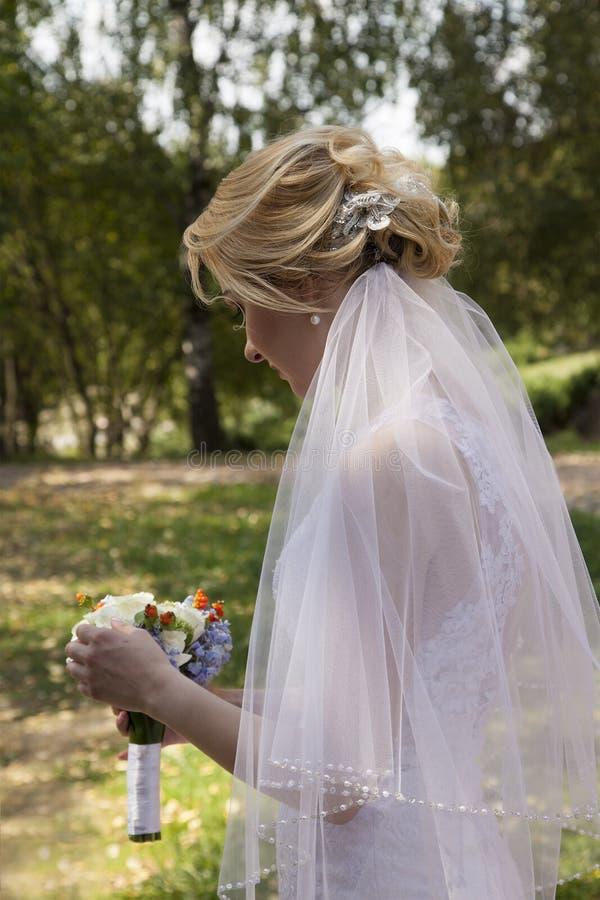Jeune belle jeune mariée tenant le bouquet de mariage image libre de droits