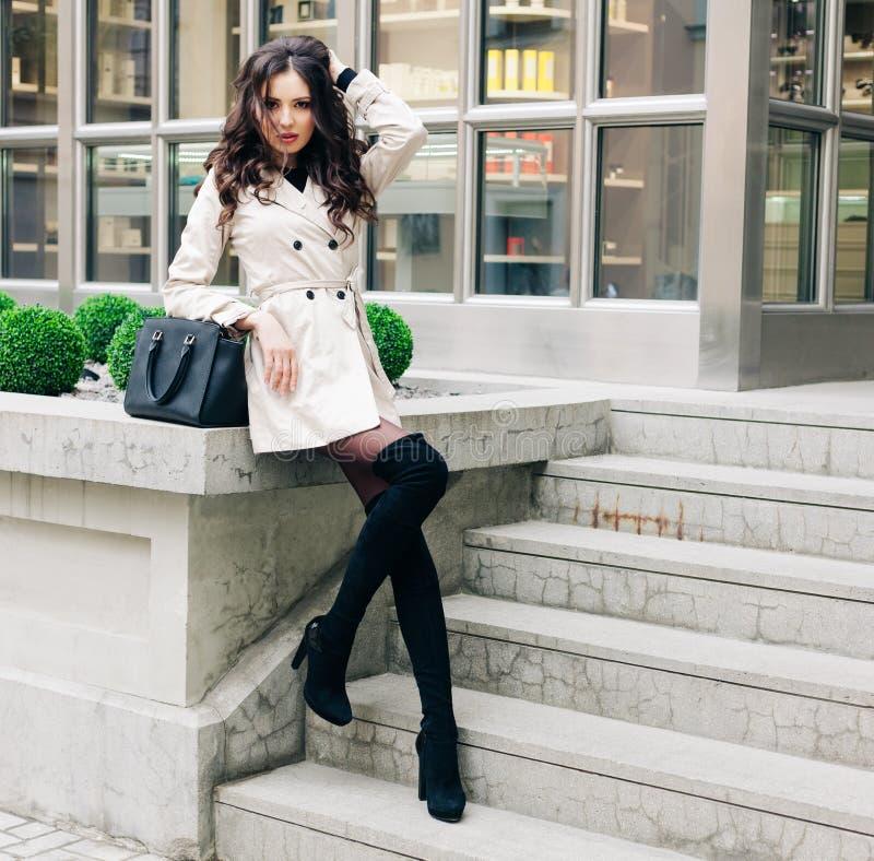 Jeune belle jolie fille marchant et posant le long de la rue avec le sac à main noir images libres de droits