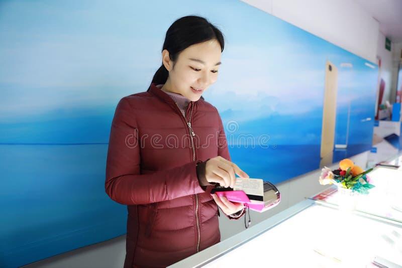 Jeune belle main heureuse de femme avec le grand coup de carte de crédit par le terminal à vendre photos libres de droits