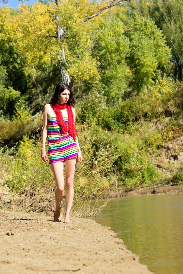 Jeune belle marche de femme extérieure dans le jour ensoleillé photographie stock