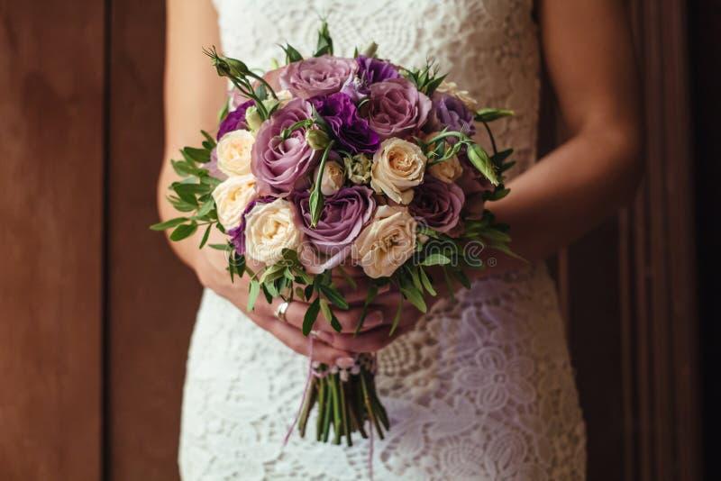 Jeune belle jeune mariée dans la robe blanche tenant le bouquet de mariage, bouquet de jeune mariée de jet crème rose, rosier, po images stock