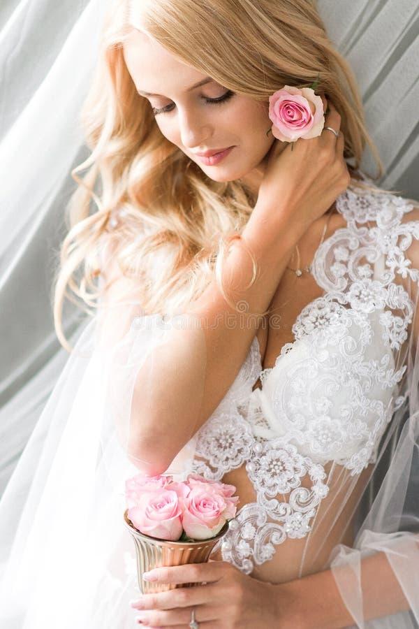 Jeune belle jeune mariée fixant un petit bourgeon de rose de rose photos stock