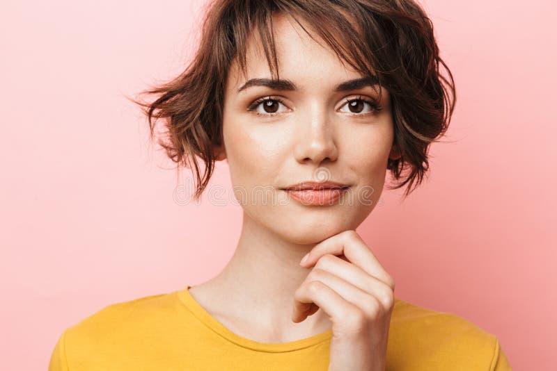Jeune belle pose de femme d'isolement au-dessus du fond rose de mur photo stock