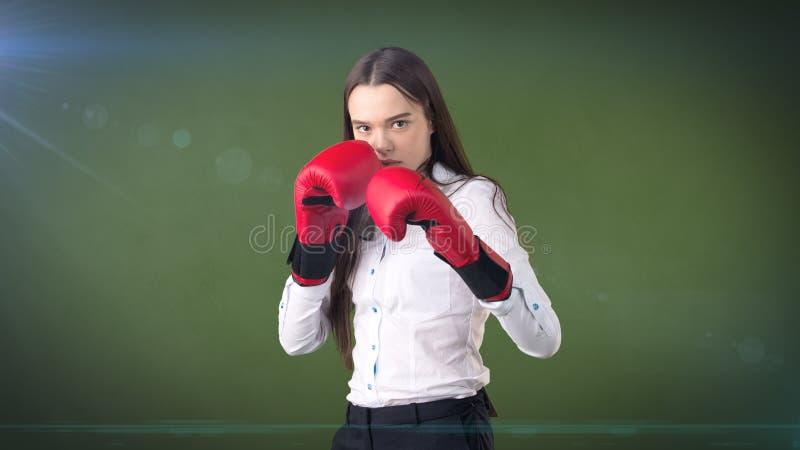 Jeune belle robe de femme dans la chemise blanche se tenant dans la pose de combat avec les gants de boxe rouges Concept d'affair photos libres de droits
