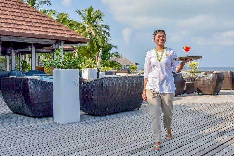 Jeune belle serveuse marchant avec le cocktail sur le plateau à la barre tropicale d'île images libres de droits