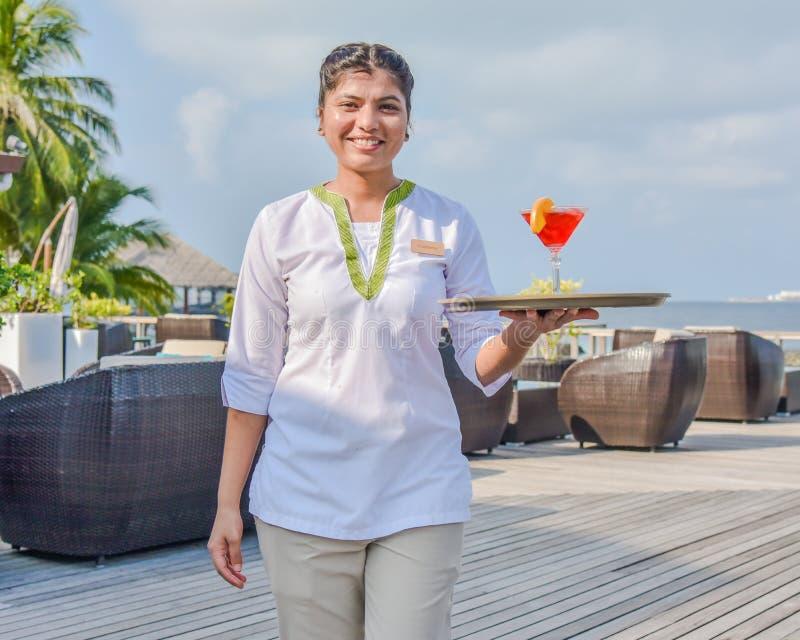 Jeune belle serveuse souriant avec le cocktail sur le plateau à la barre tropicale d'île photographie stock libre de droits